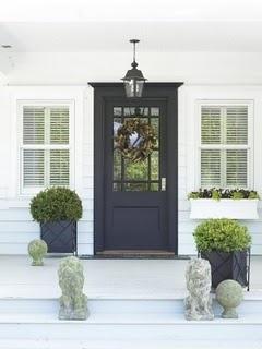 Black front door with shrubs