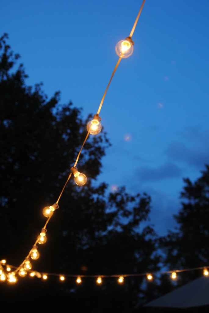 LOVE THIS: how to hang outdoor lights! What an easy and inexpensive way to add magic to your deck, patio or party... no pergola or fancy DIY skills needed!