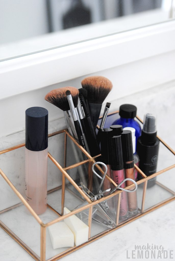 copper and glass organizer on bathroom vanity