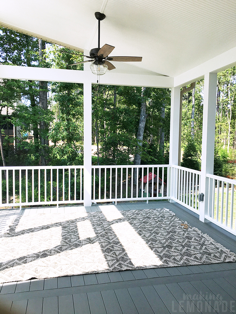 screened porch with gray deck boards and white railing