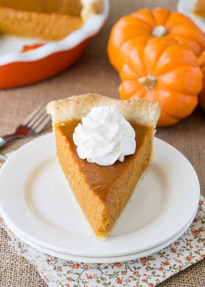 A slice of pumpkin pie with whipped cream on the top