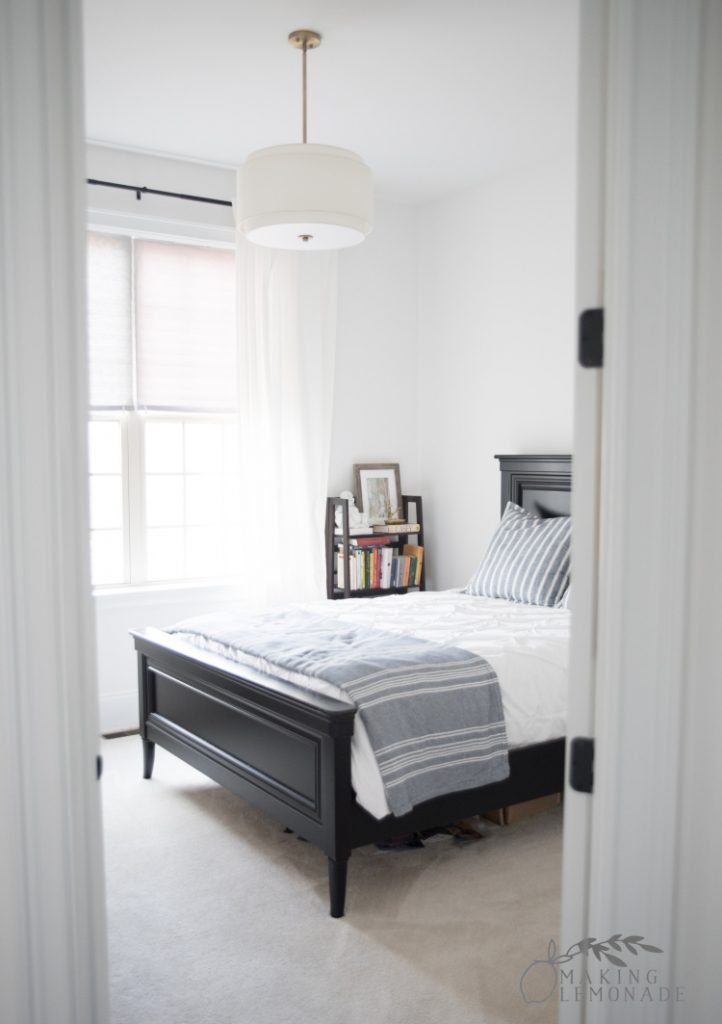 guest room with bed and white curtains