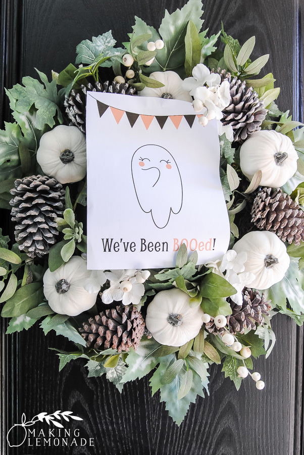 fall wreath with 'We've Been BOO-ed' sign on front door