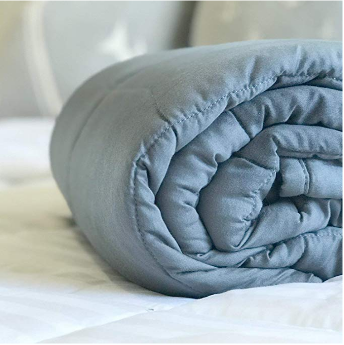 weighted blanket folded on bed