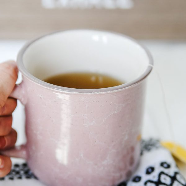 mug of tea with hand