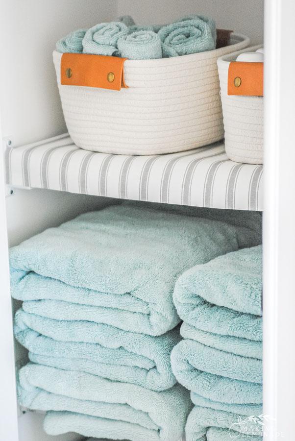 baskets and towels on linen closet shelf