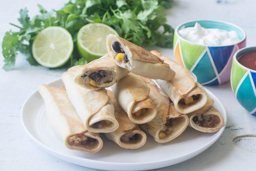 white plate with taquitos stacked on it with colorful dishes of sour cream and salsa and lime and cilantro in the background
