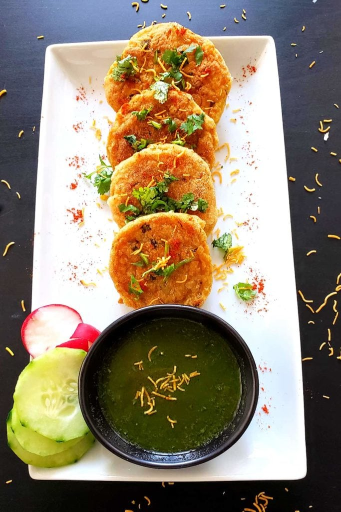 aloo tikki on a white rectangle plate with sliced radishes and cucumbers and a black bowl of green dipping sauce