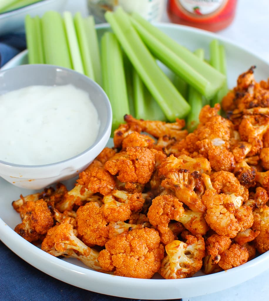 white bowl of buffalo cauliflower with white bowl of ranch dip and celery sticks