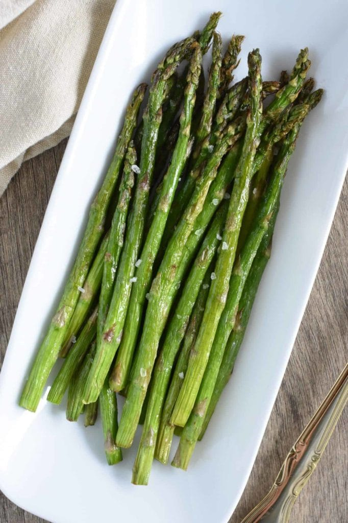 asparagus stems in a white serving dish on a wood surface