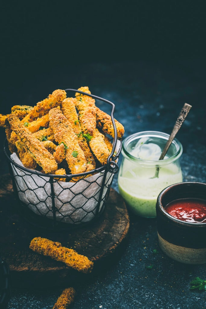 a black basket of zucchini fries with a glass bowl of dip and a ceramic bowl of dip on the side on a black surface