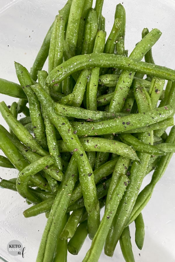 green beans with seasoning on a white background