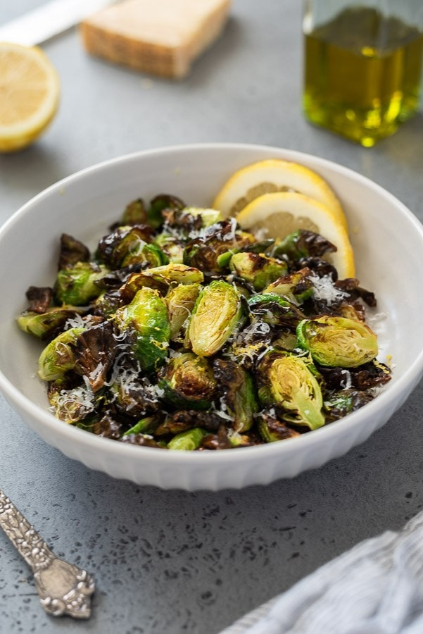 Brussels sprouts in a white bowl with a lemon on a grey surface