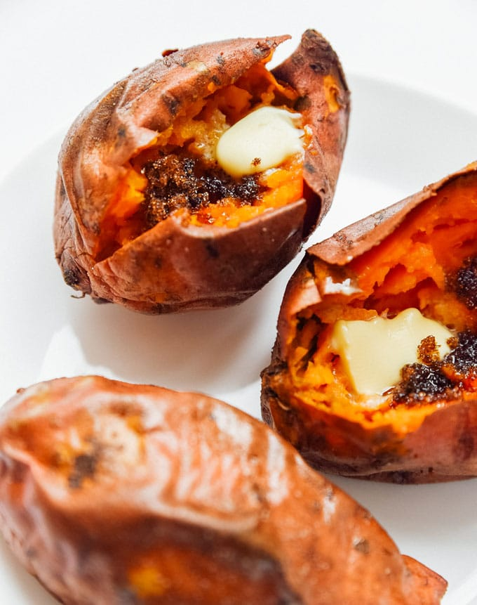 3 sweet potatoes with butter and cinnamon on a white plate