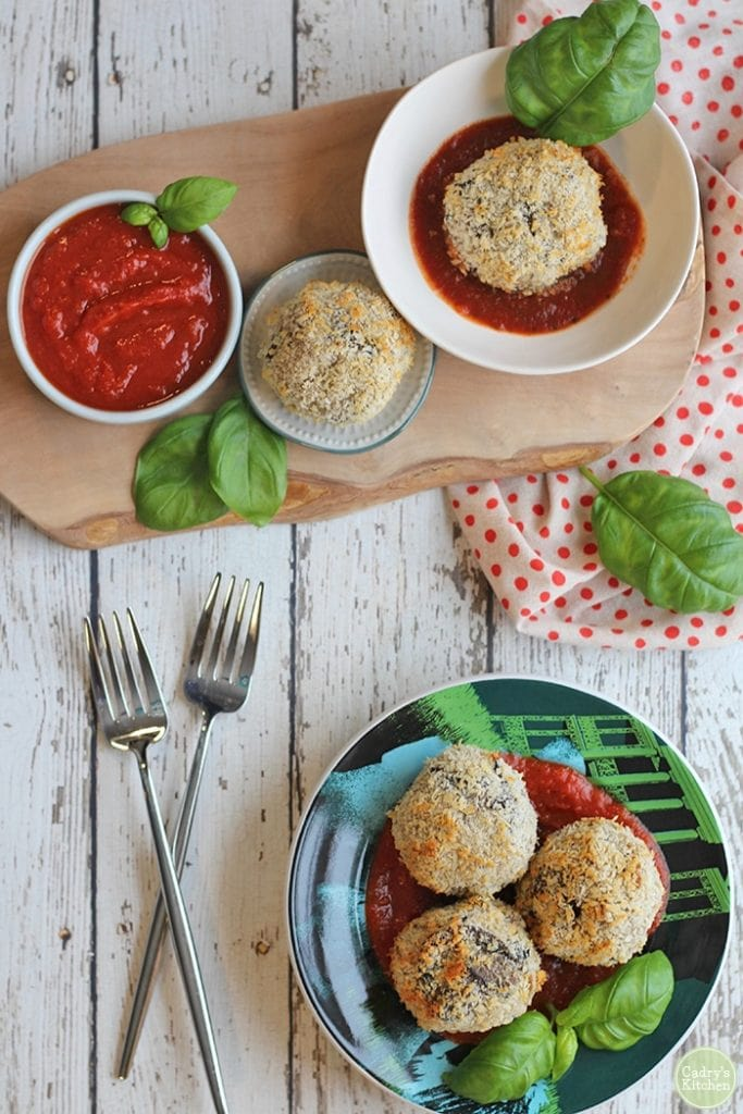 rice balls on plates on a bed of marinara with green basil leaves