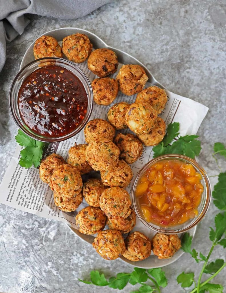 salmon croquette balls on a plate with a dark red jelly dip and an orange colored dip sauce