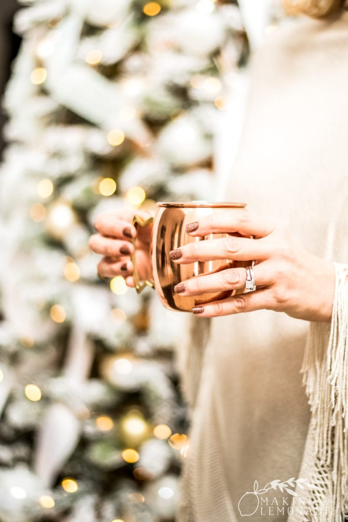 hand holding Yule Mule by Christmas tree