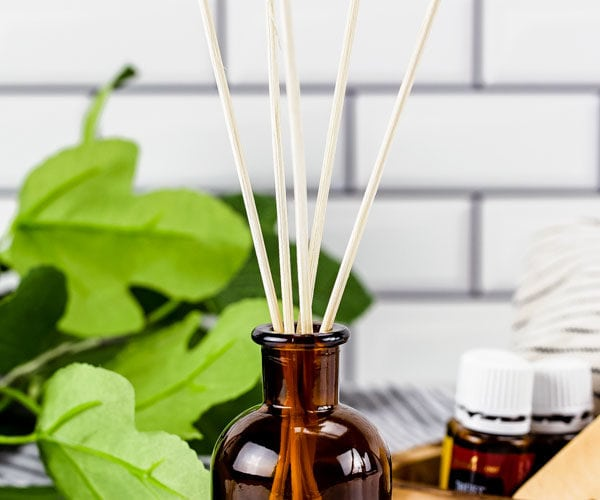 A brown essential oil glass jar with reed diffusers in it